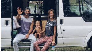 The Fell family, consisting of an attractive young man and woman and their 1-year old, sits in the open door of their home, a white panel van
