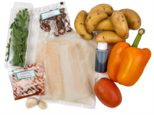 A collection of food box ingredients, including vegetables, spices, and either fish or chicken