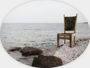 An ordinary desk chair on a beach by the sea.